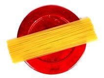 Ongekookte spaghetti op rode plaat Stock Foto's