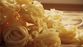 Ongekookte tagliatelle, Italiaanse deegwaren op een houten lijst stock video