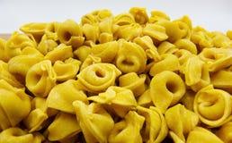 Ongekookte tortellini dichte omhooggaand op witte achtergrond, Italiaanse deegwaren royalty-vrije stock afbeeldingen