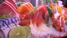 Ongekookte verse zalm en rode tonijnvissen en saba en pijlinktvis en krab met groente en vruchten geplaatst gediende stukken stock videobeelden