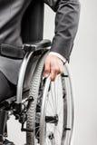 Ongeldige of gehandicapte zakenman in de zwarte rolstoel van de kostuumzitting stock afbeelding