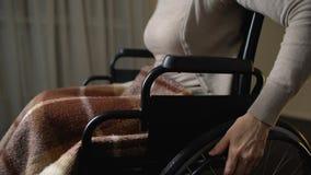 Ongeldige vrouw die in rolstoel zich thuis voor bejaarden, liefdadigheidsstichtingen bewegen stock videobeelden