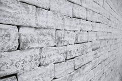 Ongelijke metselwerkbakstenen muur in zwart-witte selectieve nadruk die uit een kant wordt genomen Stock Foto's