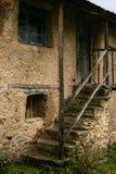 Ongelijke steentreden in een oud huis met gras en mos en houten deurkader royalty-vrije stock afbeelding
