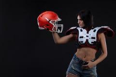 Ongelooflijk mooi, atletisch donkerbruin meisje in shoulderpads en Amerikaanse voetbalhelm het aantonen overweldigende verbazende stock foto