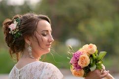 Ongelooflijk mooie bruid met boeket van rozen Romantische toebehoren van fiancee Langharig meisje in huwelijkstoga Stock Afbeeldingen