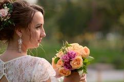 Ongelooflijk mooie bruid met boeket van rozen Romantische toebehoren van fiancee Langharig meisje in huwelijkstoga Stock Afbeelding