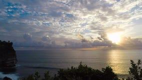 Ongelooflijk mooie mening van de zonsondergang op de oceaan Heel wat witte wolken en overzeese golven Het water raakte de rots op stock videobeelden