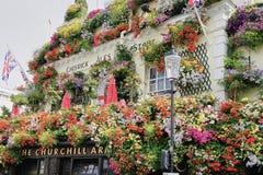 Ongelooflijke Bloemvertoning op Buitenkant van de Churchill-Wapenbar in Londen stock afbeeldingen
