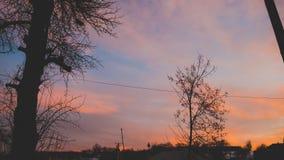 Ongelooflijke kleurrijke zonsondergang met hemel-glanzende kleuren op de achtergrond van dorpshuizen royalty-vrije stock afbeelding