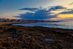 Ongelooflijke zonsondergang over kust van Kreta met hotels en stranden op de kust Vulkanische rots in de voorgrond royalty-vrije stock afbeelding