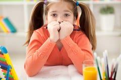 Ongelukkig bored roodharig meisje die haar thuiswerk thuis doen Stock Afbeelding
