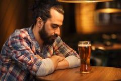 Ongelukkig eenzaam mens het drinken bier bij bar of bar Stock Afbeeldingen
