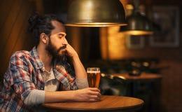 Ongelukkig eenzaam mens het drinken bier bij bar of bar stock foto