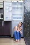 Ongelukkig en hongerig meisje dichtbij lege koelkast Stock Foto