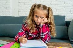 Ongelukkig jong elementair studentenschoolmeisje die en thuiswerk thuis bestuderen doen stock afbeelding