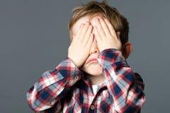 Ongelukkig jong kind die zijn ogen behandelen met handen voor droefheid royalty-vrije stock foto