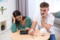Ongelukkig jong paar met spaarvarken en geld Financi?le problemen royalty-vrije stock foto