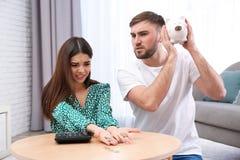 Ongelukkig jong paar met spaarvarken en geld thuis royalty-vrije stock afbeeldingen