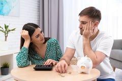 Ongelukkig jong paar met spaarvarken en geld thuis stock fotografie