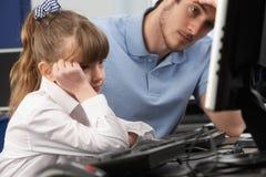 Ongelukkig leraar en meisje die computer in klasse met behulp van stock foto's