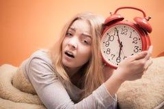 Ongelukkig meisje in bed met wekker stock fotografie