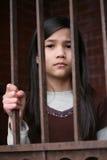 Ongelukkig meisje dat zich achter staven bevindt stock fotografie