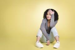Ongelukkig meisje die droevig op gele achtergrond zijn Stock Fotografie