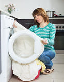 Ongelukkig meisje die wasmachine thuis met behulp van royalty-vrije stock fotografie