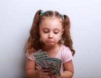 Ongelukkig verward grimassen trekkend jong geitjemeisje die op dollars in handen kijken Stock Foto's