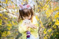 Ongelukkig weinig droevig stuk speelgoed van het de holdingskonijn van het konijntjesmeisje in de tuin van de de lentebloesem royalty-vrije stock fotografie