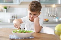 Ongelukkig weinig jongen die plantaardige salade eten bij lijst stock afbeeldingen