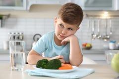 Ongelukkig weinig jongen met plaat van groenten bij lijst stock afbeelding