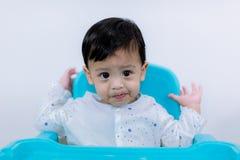 Ongelukkig Weinig kindzitting op zijn stoel die op een witte achtergrond eet droevig en ongelukkig kind op kleine stoel stock fotografie