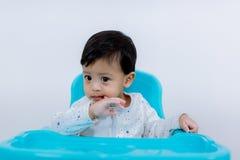 Ongelukkig Weinig kindzitting op zijn stoel die op een witte achtergrond eet droevig en ongelukkig kind op kleine stoel royalty-vrije stock afbeelding
