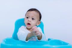 Ongelukkig Weinig kindzitting op zijn stoel die op een witte achtergrond eet droevig en ongelukkig kind op kleine stoel stock afbeeldingen