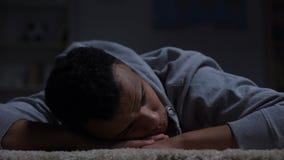 Ongelukkige Afro-Amerikaanse tiener die op vloer liggen, die aan rassendiscriminatie lijden stock videobeelden