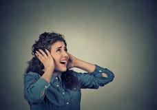 Ongelukkige beklemtoonde vrouw die haar oren behandelen die omhoog einde die hevig lawaai maken kijken stock foto