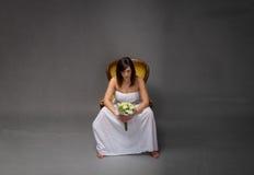 Ongelukkige bruidzitting met boeket op hand stock afbeeldingen