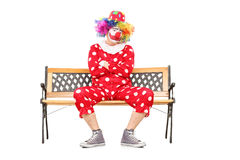 Ongelukkige clownzitting op een houten bank royalty-vrije stock foto