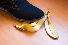Ongelukkige dag - blauwe schoen die op een banaanschil uitglijden Stock Foto