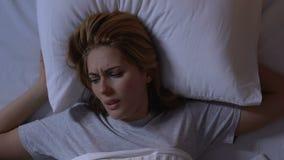 Ongelukkige dame die in bed, ongemakkelijk matras en hoofdkussen in goedkoop hotel draaien stock videobeelden