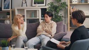 Ongelukkige familiemoeder en zoon die aan psychotherapist in moderne kliniek spreken stock video