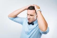 Ongelukkige gedeprimeerde mens die zijn hoofd houden stock afbeelding