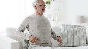 Ongelukkige hogere mens die aan rugpijn thuis 102 lijden stock videobeelden