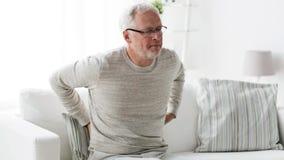 Ongelukkige hogere mens die aan rugpijn thuis 103 lijden stock videobeelden