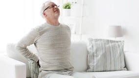 Ongelukkige hogere mens die aan rugpijn thuis 104 lijden stock videobeelden