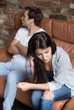 Ongelukkige jonge man en vrouw in ruziezitting op laag stock fotografie