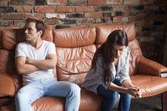 Ongelukkige jonge man en vrouw in ruziezitting op laag royalty-vrije stock fotografie