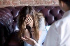 Ongelukkige jonge vrouw bij een ontvangst van de psycholoogadviseur royalty-vrije stock foto